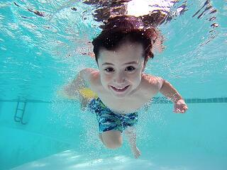 A child swims in clear pool water